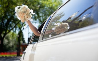 Bride waving hand holding bouquet